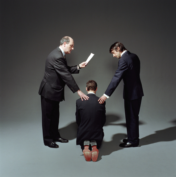 Man kneeling, flanked by two businessmen with hands on shoulders