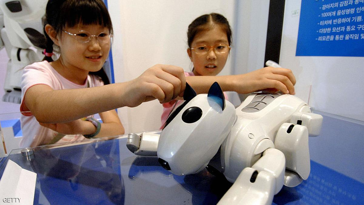 """TO GO WITH """"SKOREA-SCIENCE-ROBOTS"""" South Korean children make a curious touch on an intelligent toy robot at a state-run show room in Seoul, 31 July 2007. South Korea is writing a code of ethics for robots for the first time in the world as part of efforts to lift the robot industry. The charter will be released by the end of this year in preparation for a society in which humans and robots live together. AFP PHOTO/JUNG YEON-JE (Photo credit should read JUNG YEON-JE/AFP/Getty Images)"""